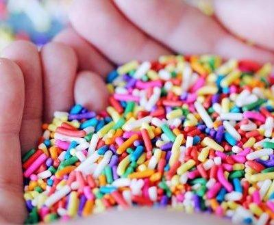 manos llenas de azucar de colores
